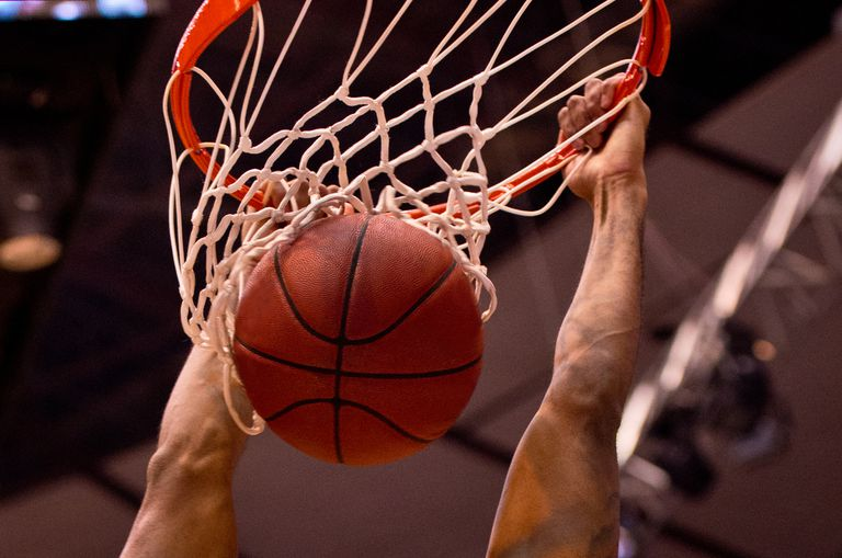 A Basketball player slamming the ball into the net