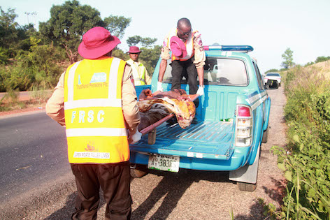 Members of the FRSC assisting wounded occupant of crashed vehicle